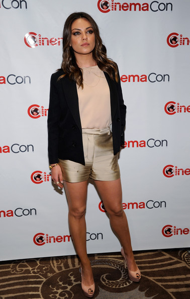 Mila Kunis manages to look both chic and sexy in tiny gold shorts